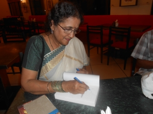 Author Mithra Venkatraj signing a book for a reader